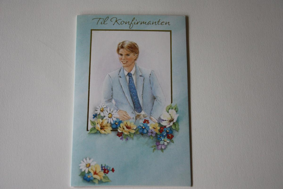 """Portrett av konfirmant i lyseblå dress mot kvit bakgrunn. Blomsterdekorajon, gullinnråmingar. """"Til Konfirmanten"""" i gullskrift."""