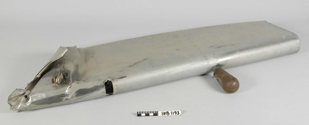 Del av flyvinge. Ser ut til å være revet av i den ene siden. Svært bulket. Bevaringstilstand god.Laget av aluminium.
