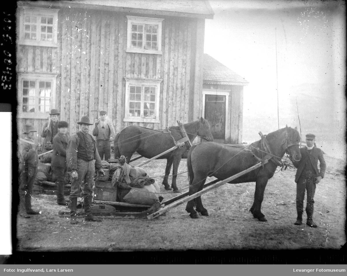 To hester med hver sin kortslede og en gruppe menn foran et våningshus.