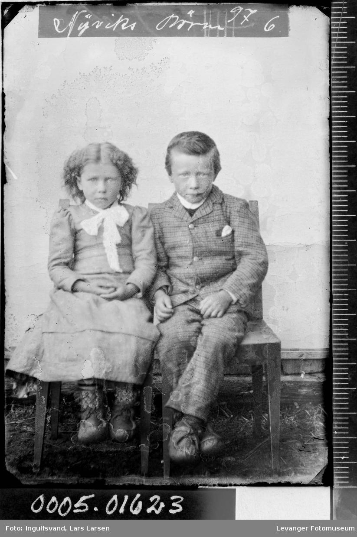 Portrett av sittende jente og gutt i helfigur.