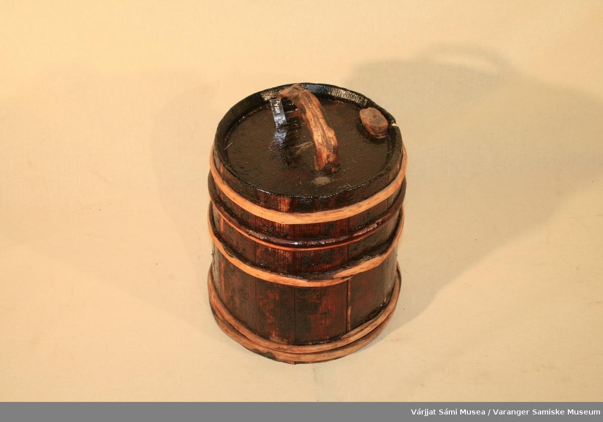 Trantønne av tre. D.D. inngravert i bunnen av tønna. Den består av 13 bord som holdes sammen av fem ringer av jern. Lokket har håndtak og en tapp til å fylle i. Tønna er innsmurt med noe slik at den har mørk farge.