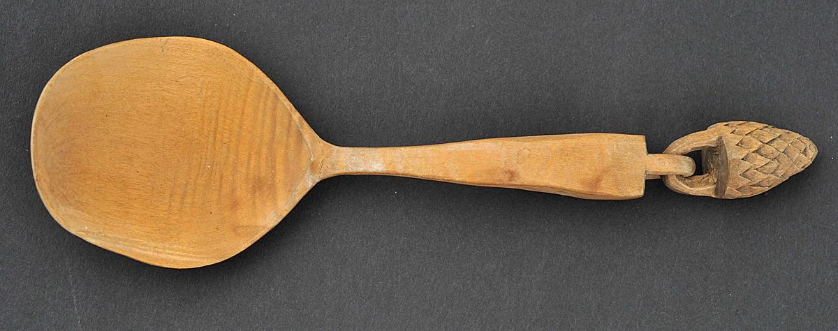 Enkel skeiform med ei lut skoren ut i enden av handtaket. I denne heng ein kongleforma drope.