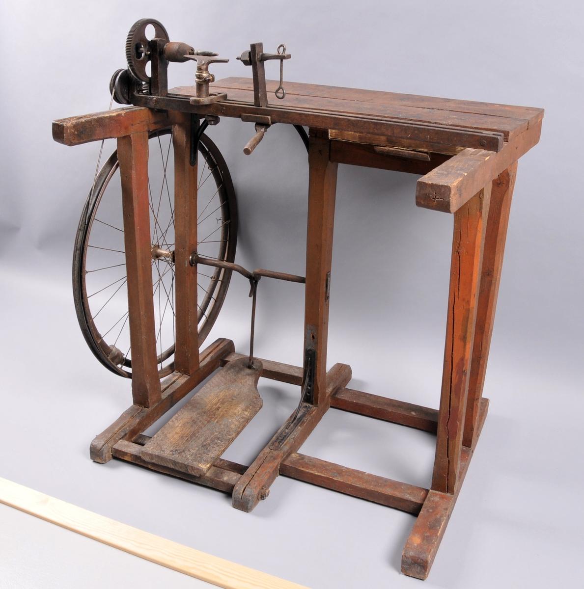 Underdel/ stativ av tre og anlegg av jern. Svinghjul av ein sykkelfelg som drivast av ein pedal.