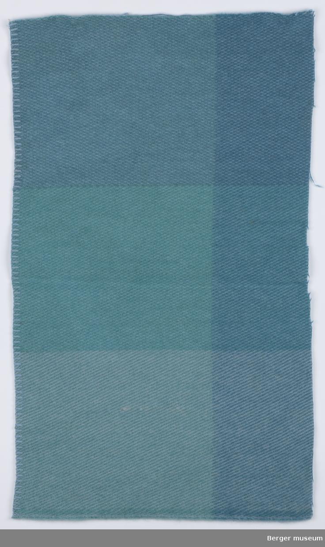 En prøve. Store felt i ruter i samme farge, men i forskjellige nyanser. Pleddet er vevet med et skråmønster i stoffet.