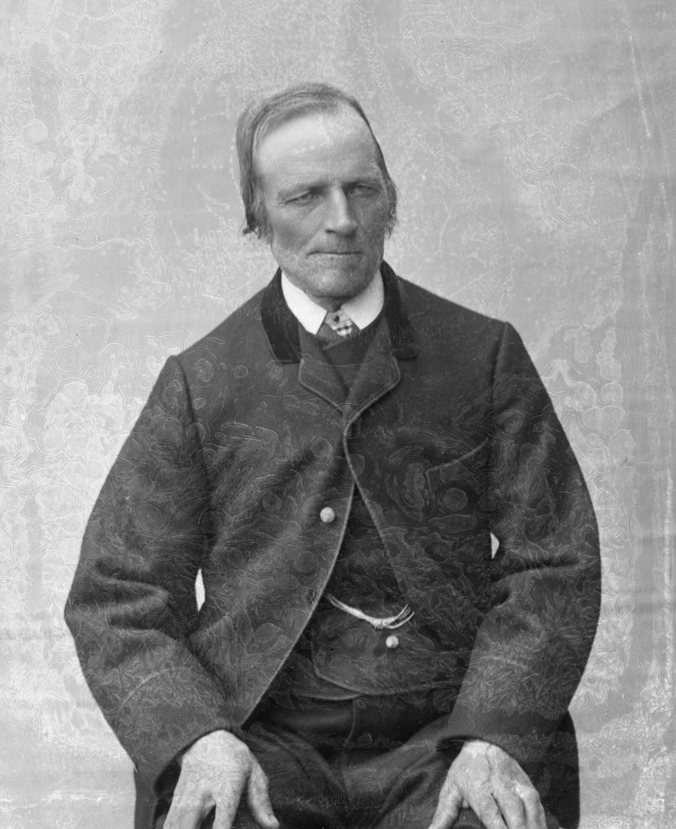 Mann sittende foran hvitt lerret