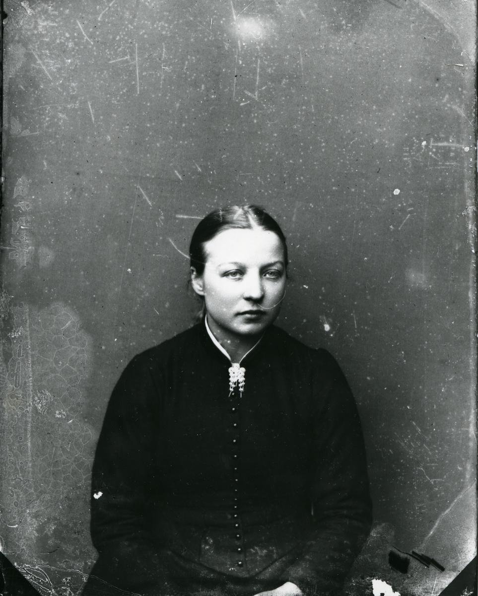 Kvinne i halvfigur foran lerret