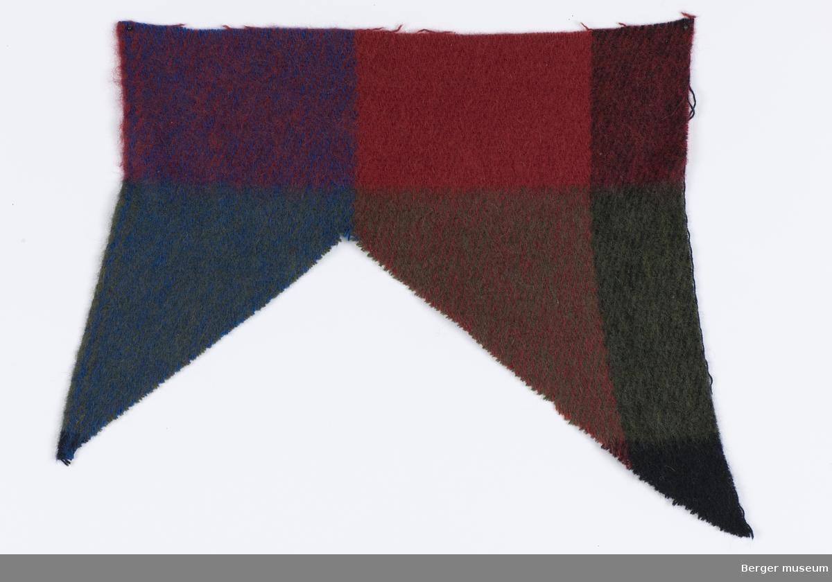 Store ruter hvor fargene består av tildels ensfargede klare farger og tildels at fargene glir over i hverandre i skrått mønster. Rutene er 15X15 cm store. Prøven er klippet i v-form.