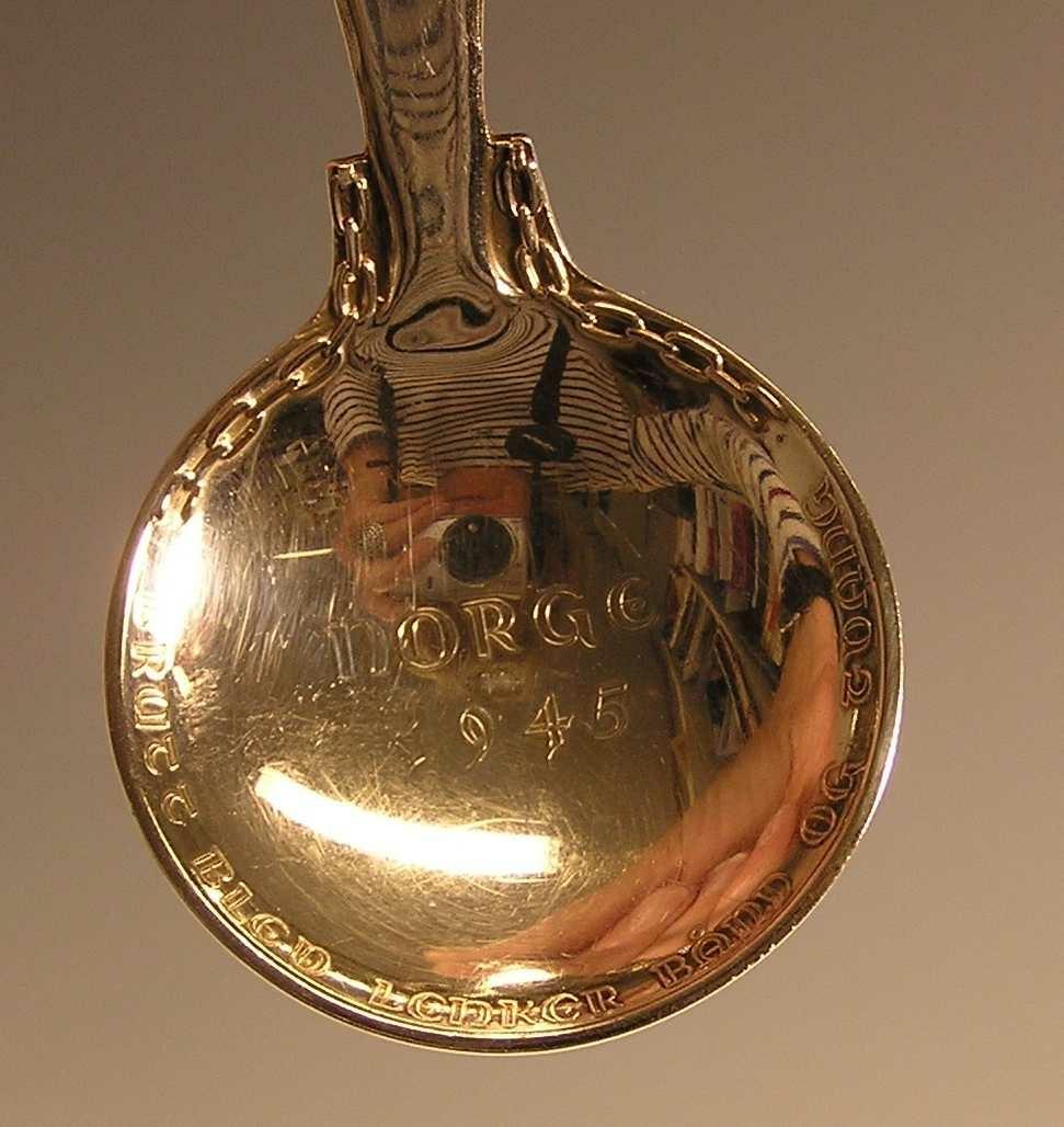 Stående mannsfigur holder høyt  et firbladformet symbol  med krone inni. Lenker på hver side av bladet mot hals.