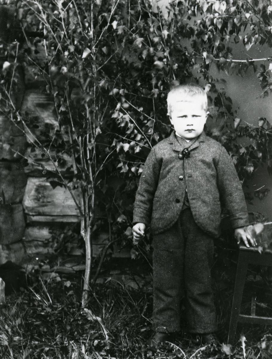 Liten gutt, foran bjørkekvister satt opp langs tømmervegg