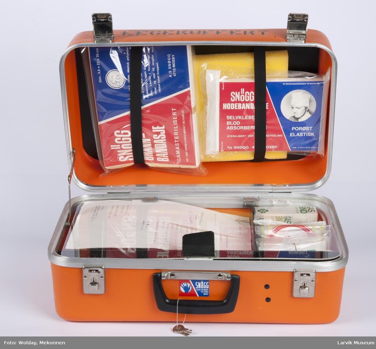 Legekoffert med diverse utstyr som bandasje, plaster, gasbind, bomuld, diverse sakser, sprøyter etc., samt liste over innhold.  Førstehjelpskoffert koffert til bruk for lege som kommer tilstede ved ulykker i bedrift.  2 nøkler henger fast i håndtaket.