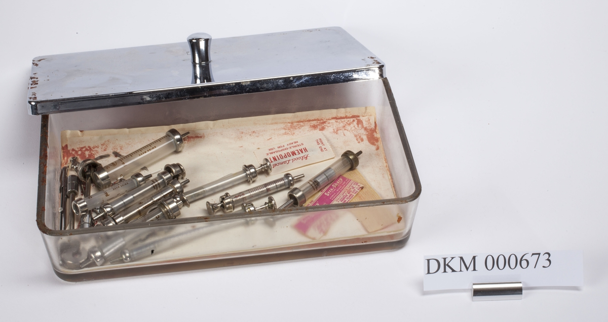 Rektangulært skrin med lokk. Skrinet inneholder flere sprøyter, nåler og deler til disse.