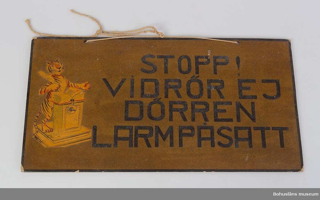 """Skylt med svart text mot brun botten:  """"STOPP!  VIDRÖR EJ  DÖRREN  LARMPÅSATT"""". Till vänster om texten en påklistrad bild - en tiger som håller en fjäderpenna i ena tassen, redo att skriva i en tjock bok med röda pärmar som ligger på en talarstol. Från boken hänger ett band med en etikett med texten: """"Tiger"""".  I bildens nedre vänstra hörn står det """"EF. - 59"""". På skyltens baksida står det textat i svart: """"TILLHÖR PORTEN""""."""