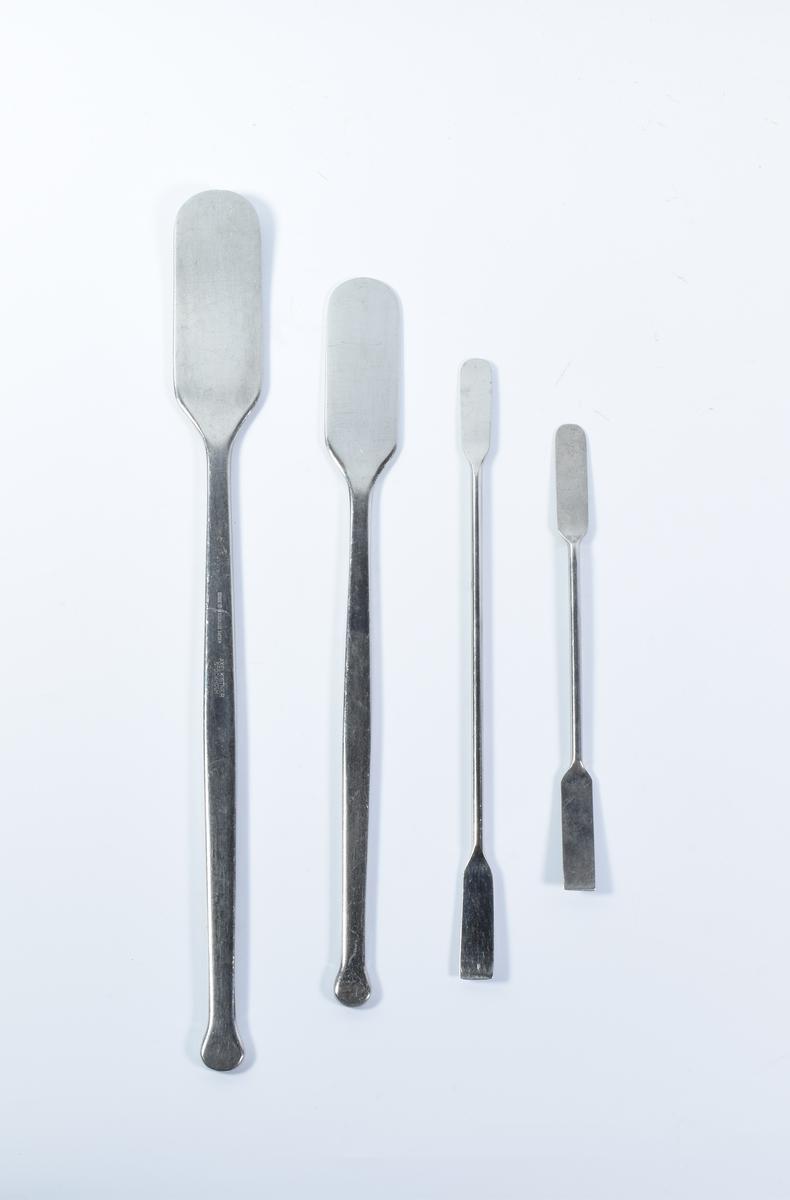15 redskaper i rustfritt stål til bruk i medikamentfremstilling.   a-f: Seks ulike typer skjeer. De tre minste skjeene er tilnærmet like.  g-j: Fire spateler i ulik størrelse. Redskap g og h er de to største. De er flate i den ene enden og avrundet i den andre. Redskap i og j er mindre og er flate i begge ender.  k: Kniv med metallskaft  l: Spatel med treskaft.  m: Redskap med metallring med rifler på innsiden og treskaft. For å sikre sterile flasker ble korken skrudd på med dette redskapet.  n-o: To veieskip.