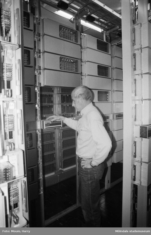 Nya telefonnummer i Kållered och Lindome, år 1984. Stationsreparatör Lars Åke Hansson vid Kållereds telestation. Här och på stationerna i Lindome och Hällesåker skall numren kopplas om.   Telestationen ligger (2015) fortfarande kvar intill Kållereds bibliotek.  För mer information om bilden se under tilläggsinformation.