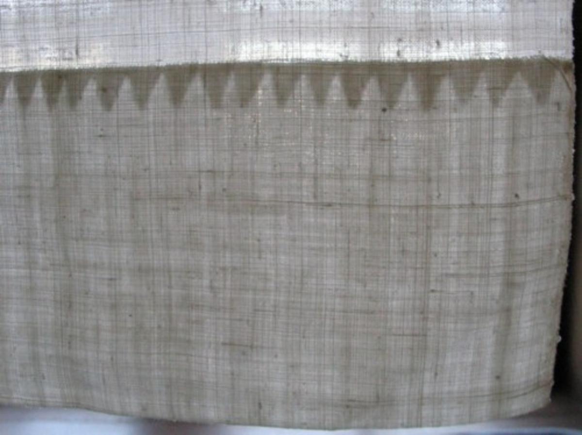 Ett klutband. Liten rullfåll i ena kanten, ca 1mm bred, i andra kanten stadkanten. Bred fåll nedtill, inne i fållen är inviket klippt i taggar. I motsatta änden är klutbandet veckat mot en avklippt hörna av kluten.