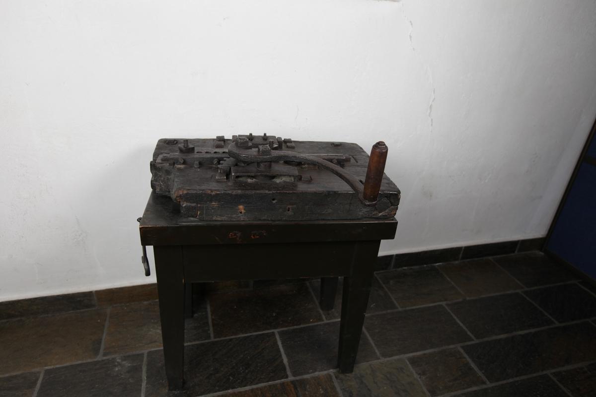 Randverket består av en tykk treplate som ligger på ett bord med fire bein. På overflaten er det bolter, tannhjul og sveiv.