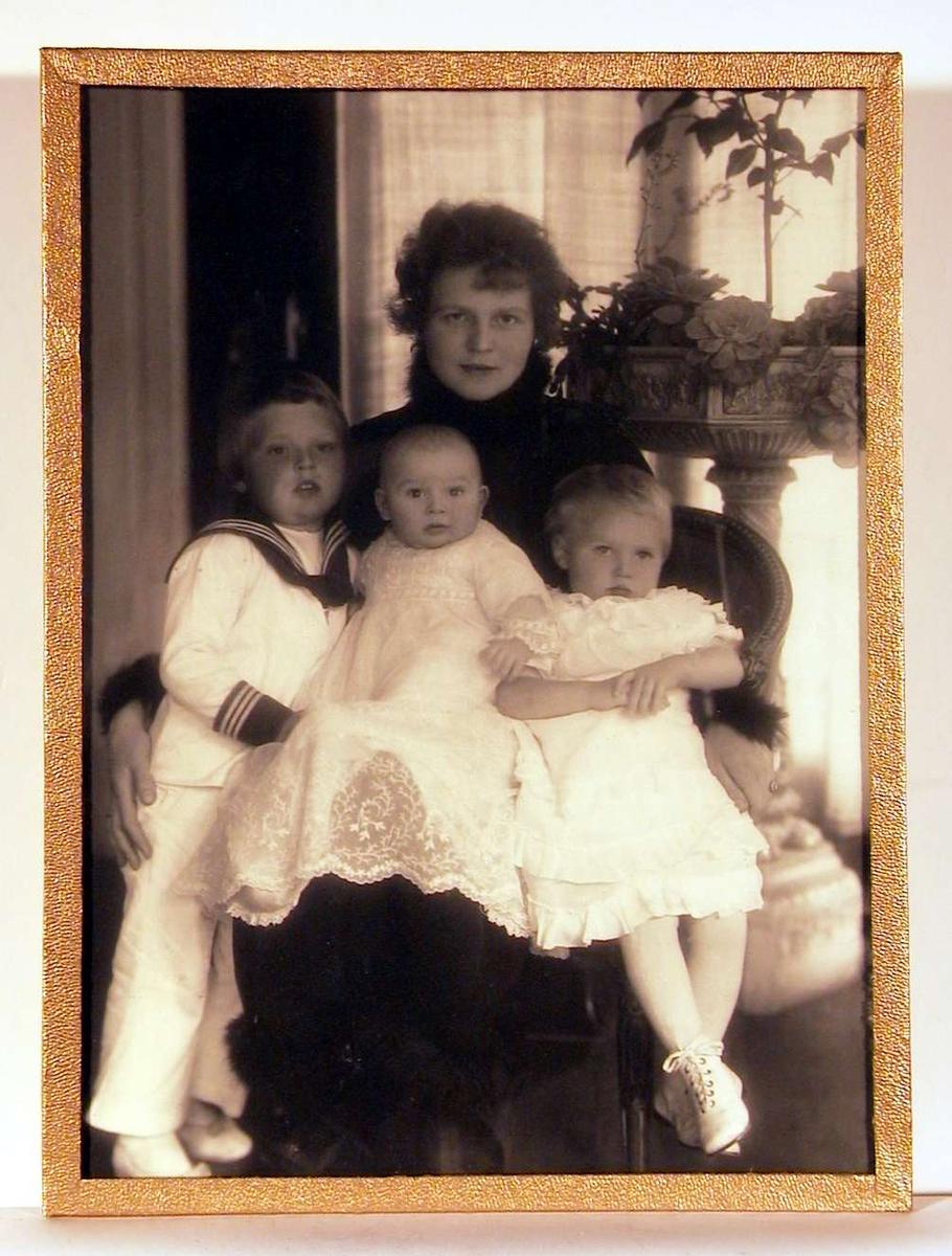Portrettfotografi; dame sittende i vid armstol i mørk helt lang kjole med fjær/dun/pels i kanten rundt hals, håndledd og nederst på kjoleskjørtet. Dels på fanget og lent inn over er tre barn i hvitt: en baby - antagelig i dåpskjole midt i fanget, til høyre en pike klemt inn på stolen, og til venstre en gutt i hvitt mattrostøy med lange hvite bukser, stående lent inn mot dåpsbarnet. I bakgrunnen en stor oppsats med forskjellige planter.