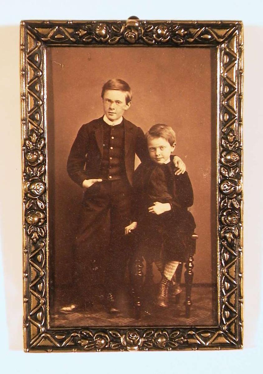 Portrettfotografi av to gutter; den yngste sittende på en stol, den eldste stående med armen om den yngstes skulder og andre armen med hånden i lommen. Begge er kledd i stastøyet og ser direkte på betrakteren.