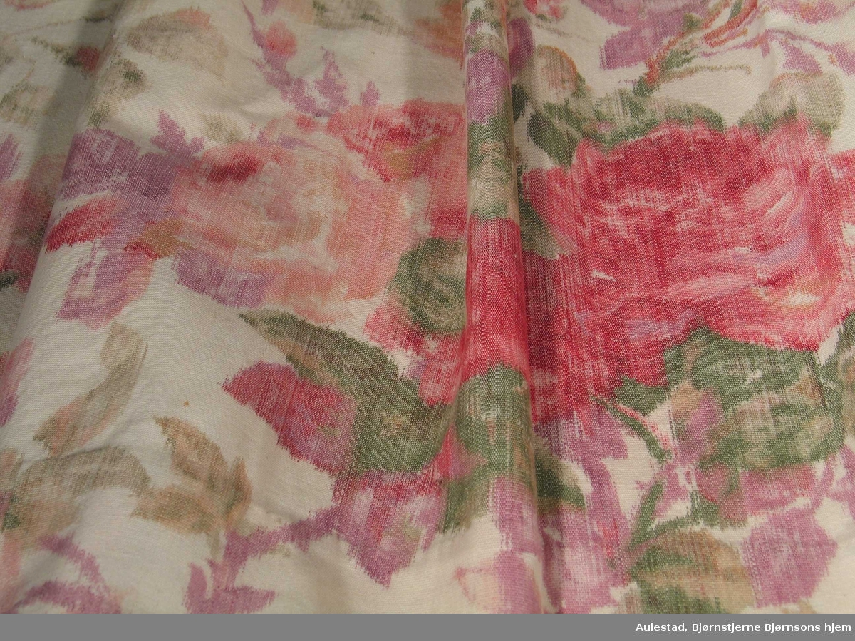 Gardin i storblomstrete bomullskretong i røde, grønne og lilla nyanser. Gardinen er foret med hvitt lerret. Det er sydd folder med metallringer langs øvre kant.