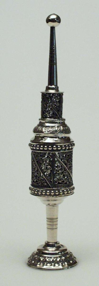 Røkeleseskar i sølv. Det har form som et lite tårn på sokkel med kule på toppen og rundt fotstykke med mønster. Karet er dekorert med perlerelieff og filigransmønster