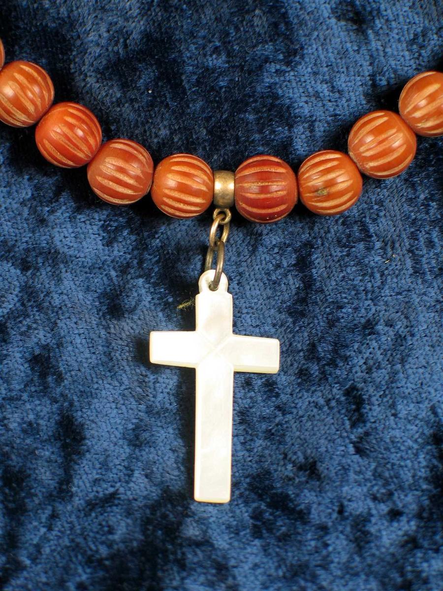 Rosenkrans av sedertre med kors i perlemor. Vedlagt notis.