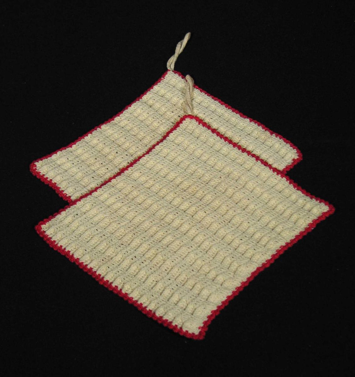 To stykker heklet gulhvit gryteklut med rød tagget kant. Heklingen består hovedsakelig av staver og danner et rutemønster i strukturen. Heklet hempe.