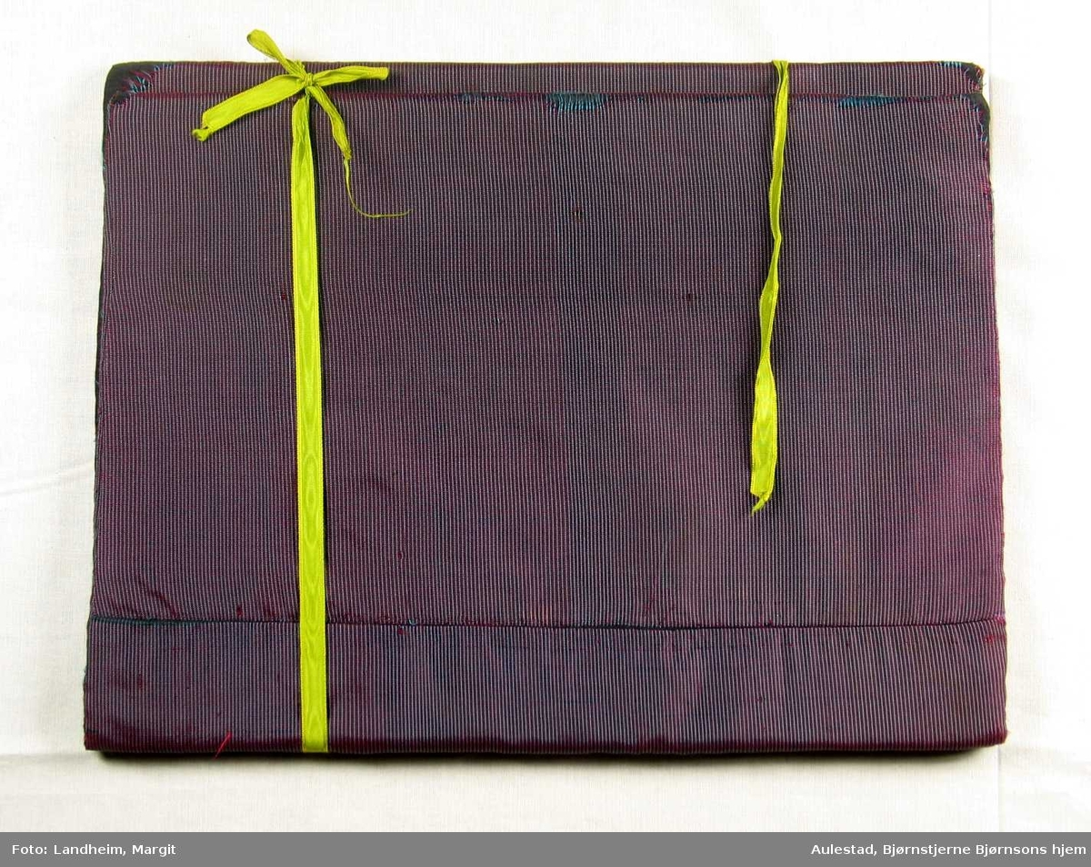 Mønstret bokomslag evt. mappe laget av to papplater,polstret og trukket med stoff. Gule pyntebånd utvendig på øverste halvdel med ender for knyting. Stoffet er smalstipete: svart og blågrønt den ene retningen og svart/rødt den andre.