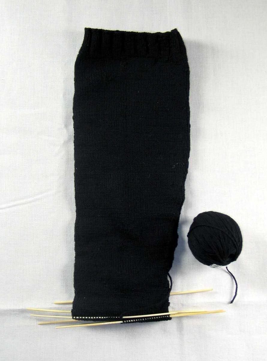 En svart strømpelegg med nøste. 3 cm vrangbord, 3 rette og 2 vrange masker. glattstrikket med felling midt bak på leggen ved en maske vrang. Fire 20 cm lange pinner av bein sitter i strikketøyet, en løs. Nøste der tråden er møllspist tvers av.