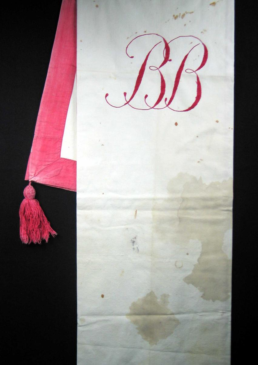 Hvit duk med påsydd rød kant og dusker i tre hjørner. Rødt brodert monogram i midten.