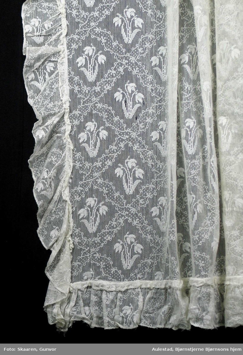 Hvit maskinvevd gardinlengde. Rutemønster på høykant med snøklokkemotiv i hver rute: tre blomster og to blad. Bunnen er gjennombrutt.