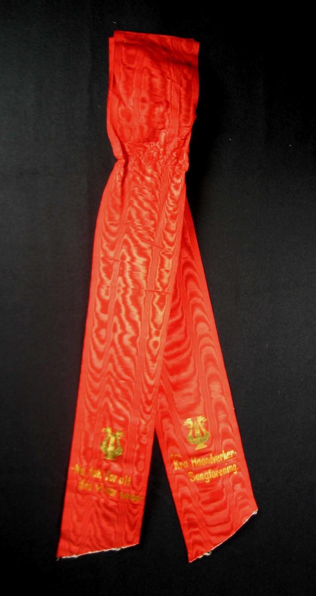 Begravelsessløyfe i mønstret rød silke med tekst i gull.