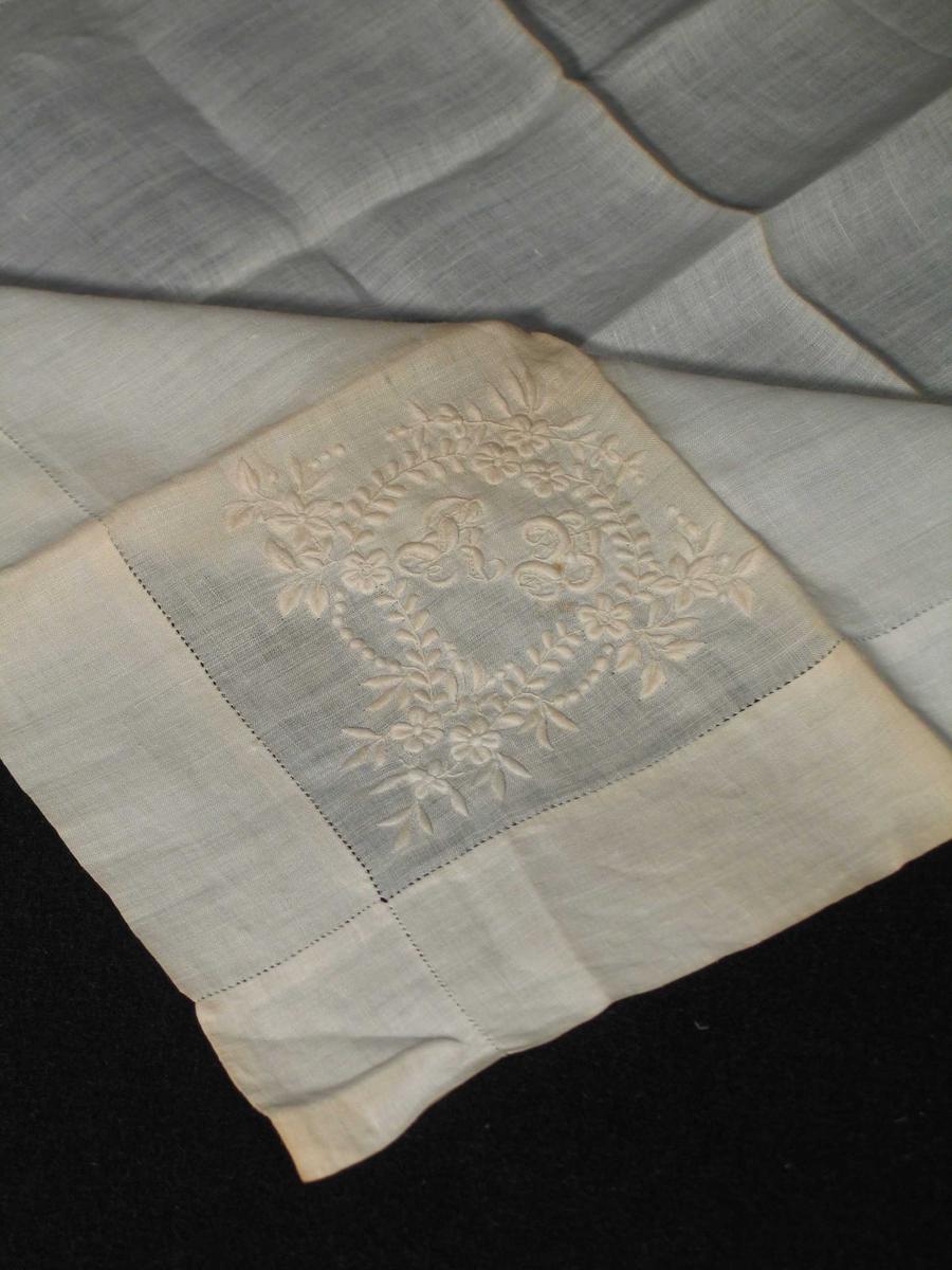 Hvitt lommetørkle i lin med brodert monogram i et skjoldformet blomstermotiv. 4 cm brede falder med stikkhullfald som krysser i hjørnene.