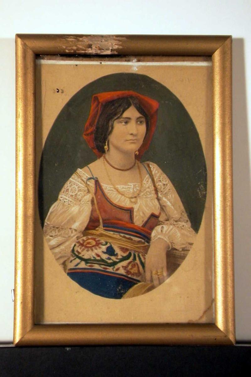 Ung kvinne lener seg mot ateliér-rekkverk, kledd i nasjonaldrakt.