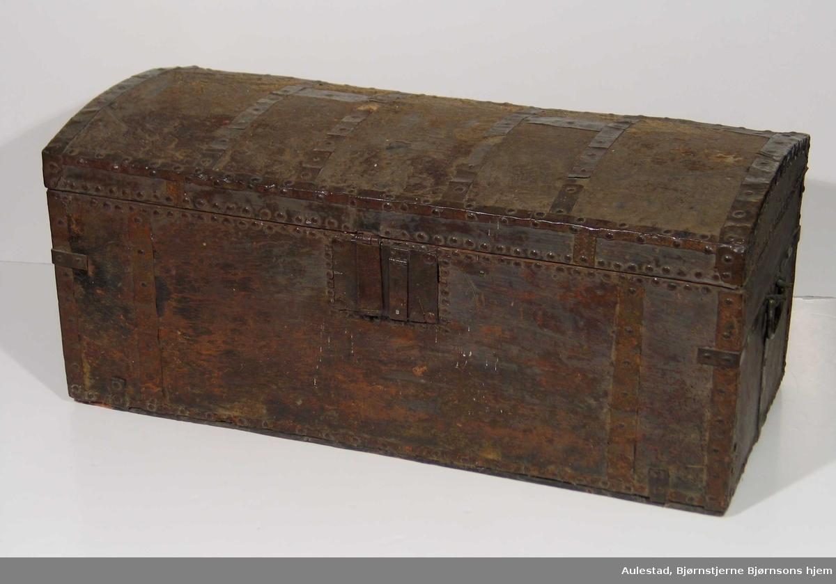 Kiste med hvelvet lokk trukket med kuskinn. Nagler og jernbeslag. Firkantet låsbeslag, komplisert låssystem. To hanker.