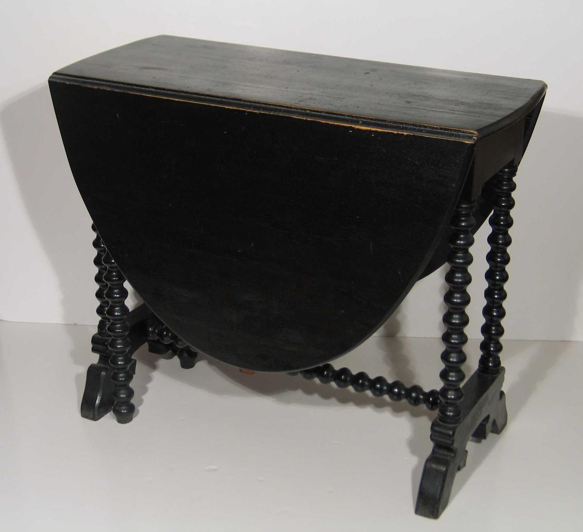 Svart klaffebord med kuledreide ben og oval plate. Rett utskåret sarg.