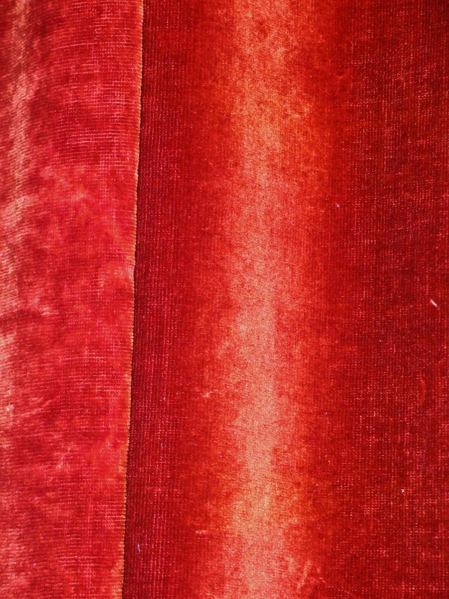 Rødbrun portiere i bomullsplysj foret med grønn sateng. (Opprinnelig svart?)Isydd feste for metallringer, samtidig lagt en liten fold. Forhenget er hengt på kroker i en trelist.  Tatt tilside med en grov, tvunnet mørk rød ullsnor med knute nederst. Oppløste trådender utenfor knuten.
