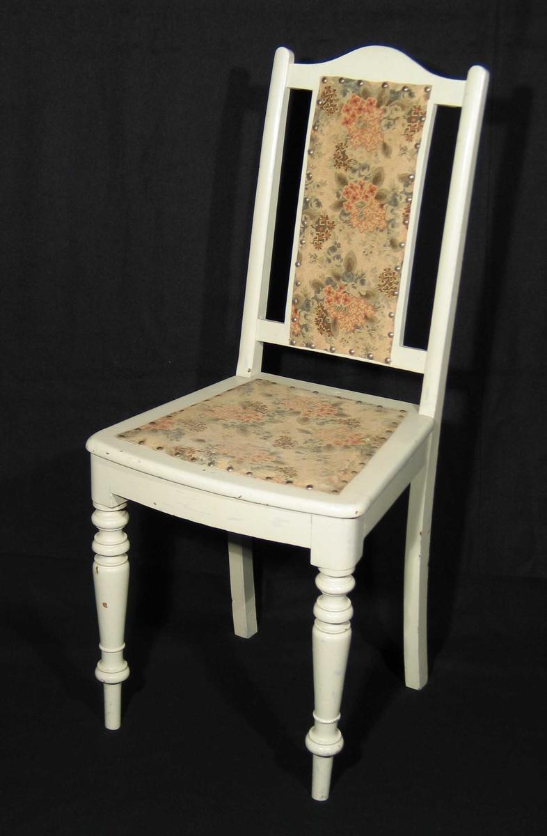 Hvitmalt stol i tre trukket med tekstil over rotting ryggbrett og sete. Skrånet ryggbrett og to akterstaver, tverrsprosse. Setet smalner bakover, buet forside. Forbenene er profilerte og rette, bakbenene er firkantete og skråner bakover.