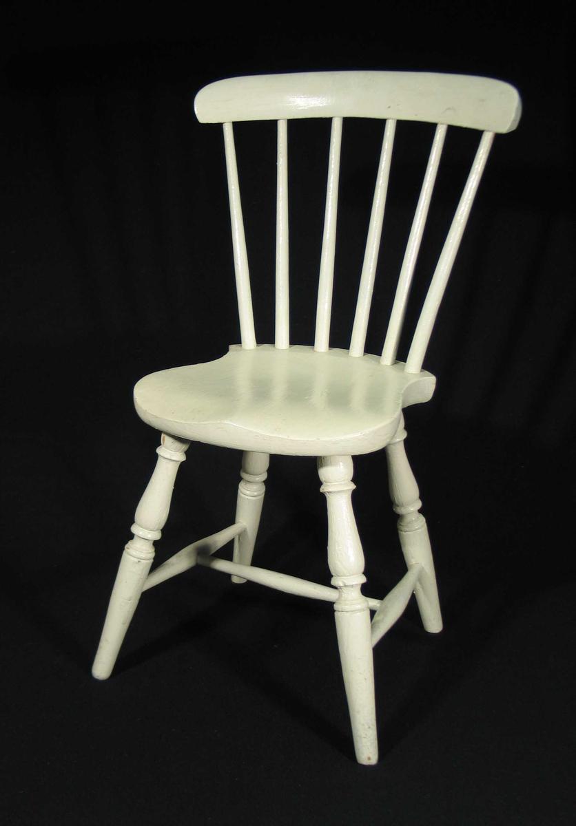 Hvitmalt pinnestol for barn. Den har dreide profilerte bein, sprosser og staver i ryggen.