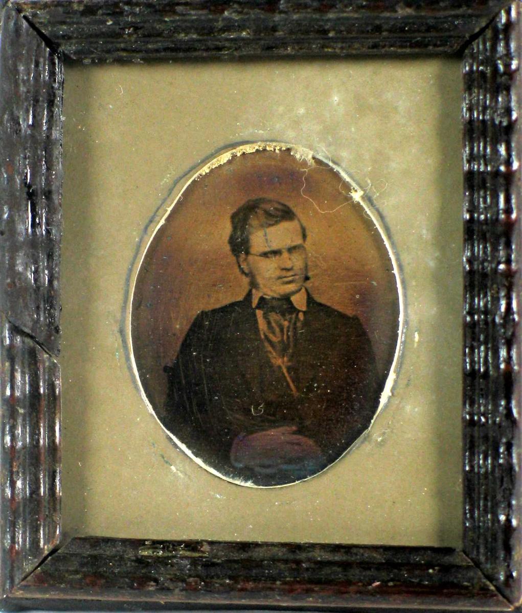 Portrett i gammel fotografiteknikk, trolig ambrotypi. Bildet har grå oval passepartout og mørk brun profilert treramme.