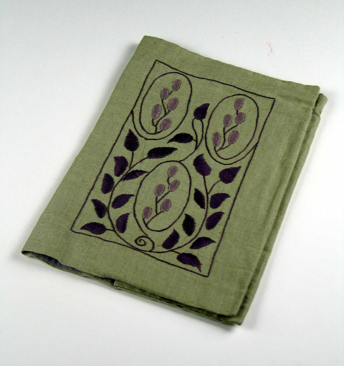 Grønt bokomslag i lin fôret med lilla silke. Forsiden har lilla blomsterbroderi. Baksiden har et brodert monogram i to lilla nyanser.