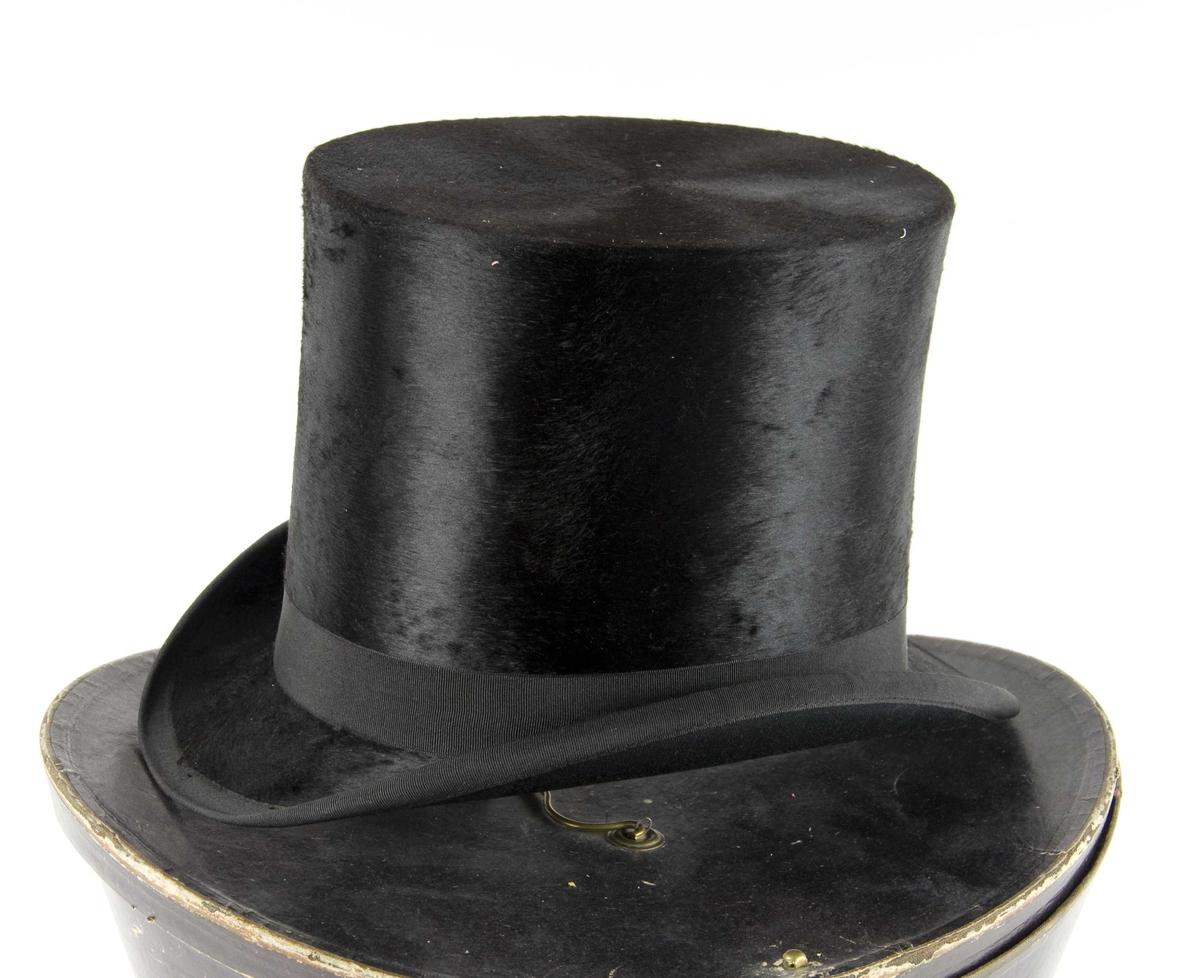 Sort flosshatt med sort ripsbånd og brun svettereim.  Det følger med en hatteeske.