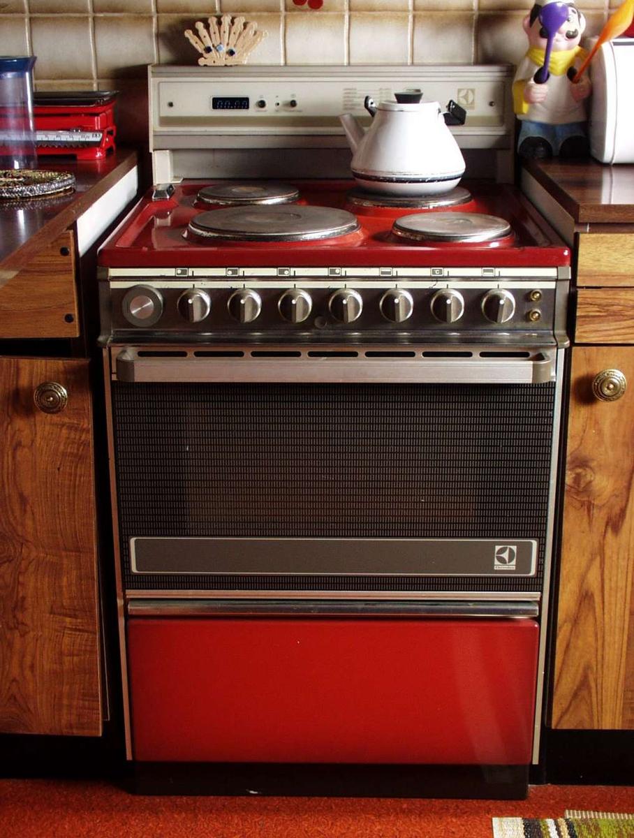 Komfyr med fire plater, stekeovn og varmeskap. Ovnen er rustrød. Ryggen har digital klokke og varselur. Veiledning for steking på døra i varmeskapet.