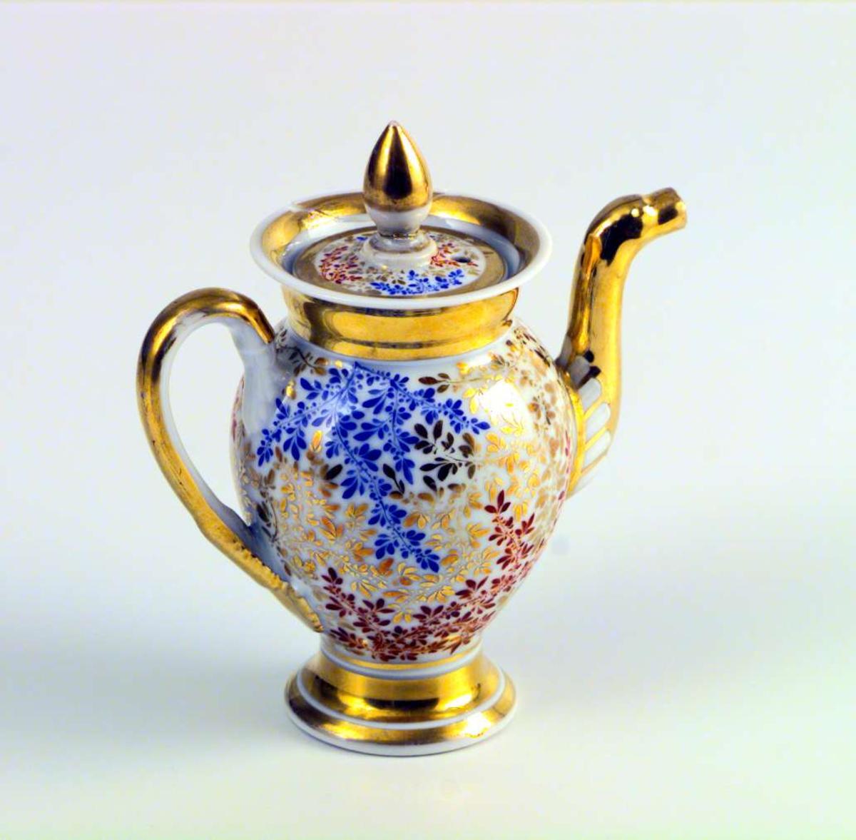 Kaffe-/tekanne med lokk i hvitt porselen malt med bladverk i rødt, blått og gull. Forgylte kanter på fotring og langs kanten på kannen. Forgylt hank og tut. Forgylt lokkgrep og forgylt kant på lokket. Kanten på kannen er limt.