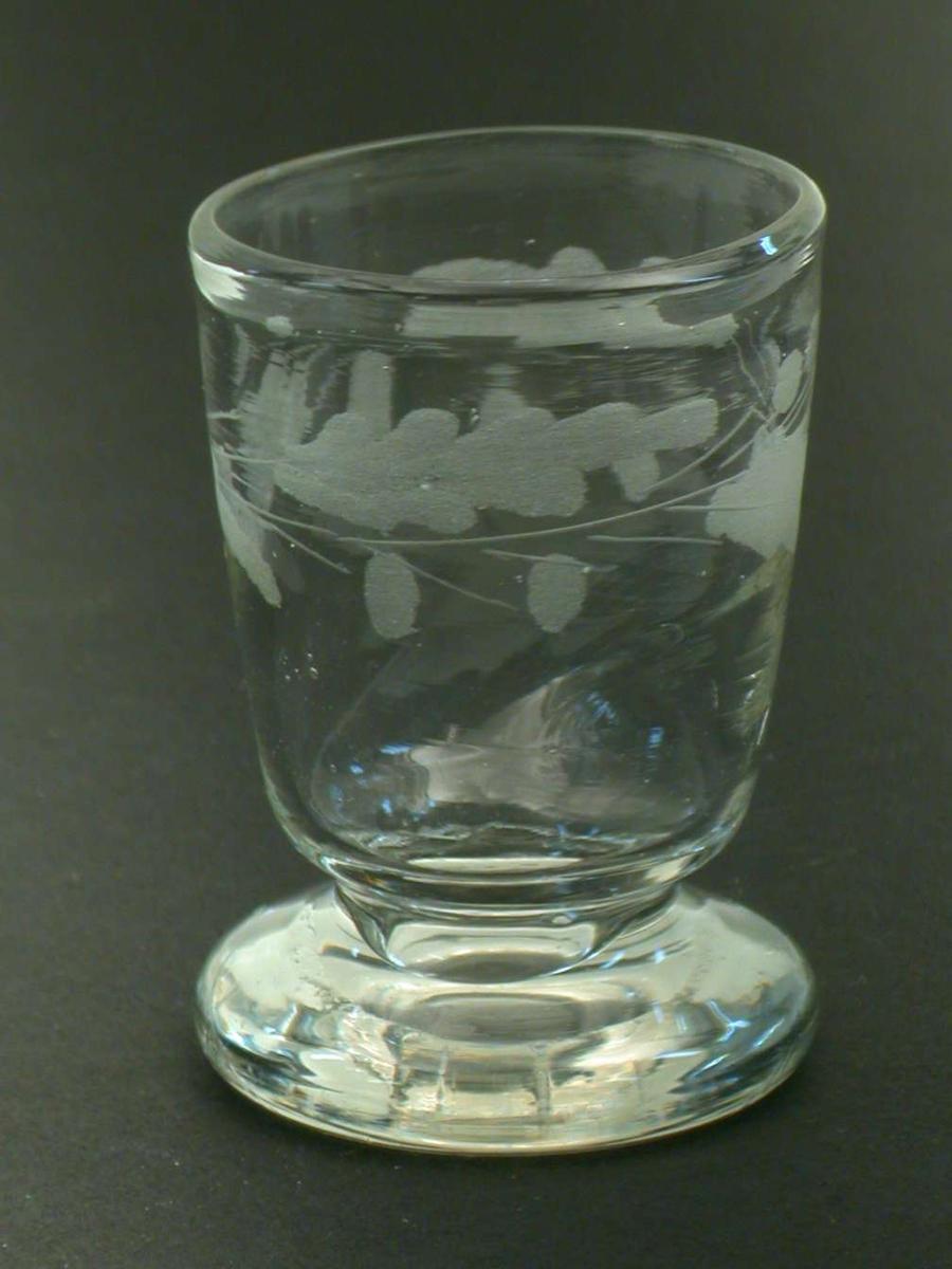 Rundbundet beger med rudimentær stett som nesten direkte forbinder begert med en tykk fot. Glasset har ekeløvsgravyr.