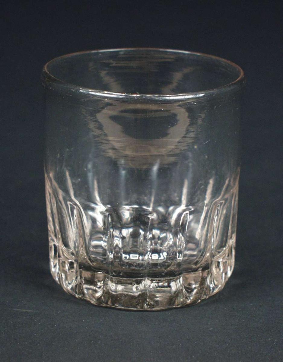 Ølglass, klart svakt grålig glass, med formede rifler halvveis opp på korpus.
