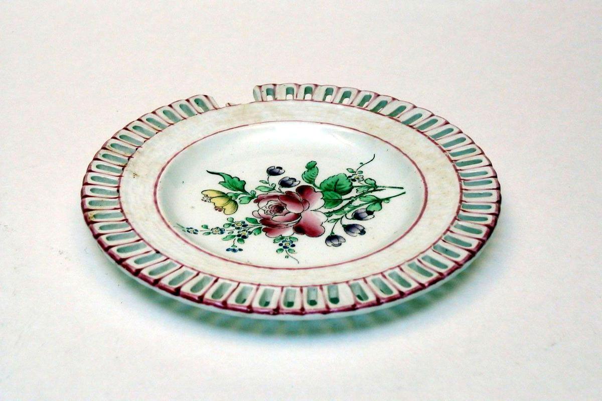 Asjett i keramikk med kremfarget glasur og med blomsterdekor. Den har 'hullfallskant'. Varemerket er initialene K G i japansk-inspirert stil, sammen med Luneville, France. Det er preget et symbol (et raster) i godset sammen med bokstavene EO. Asjetten er defekt.