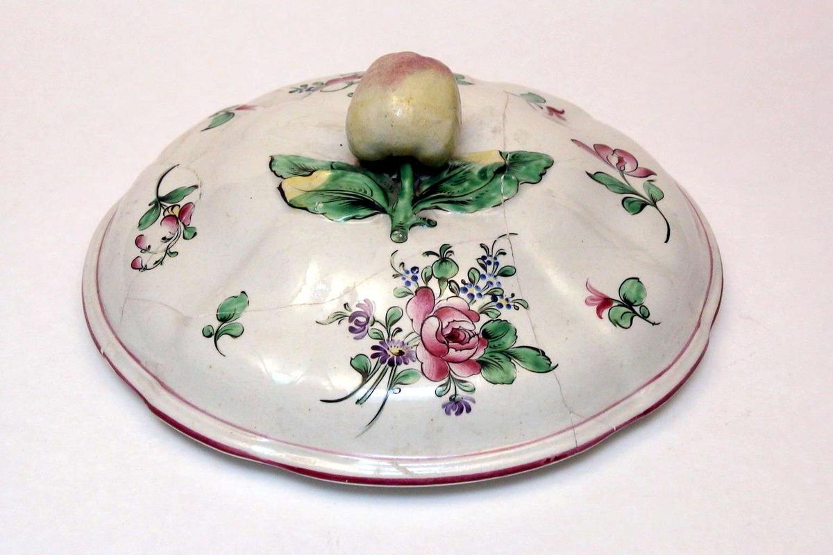 Rundt lokk i kremfarget keramikk med polykrom blomsterdekor. Lokkgrepet er et eple. Lokket er defekt. Fatet eller terrinen som lokket har hørt til, mangler.
