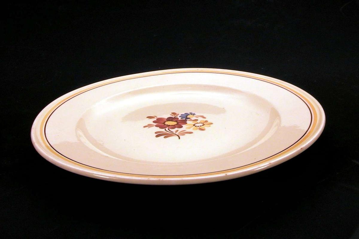 Gul tallerken med blomsterdekor på midten, langs kanten en oker og en brun linje.