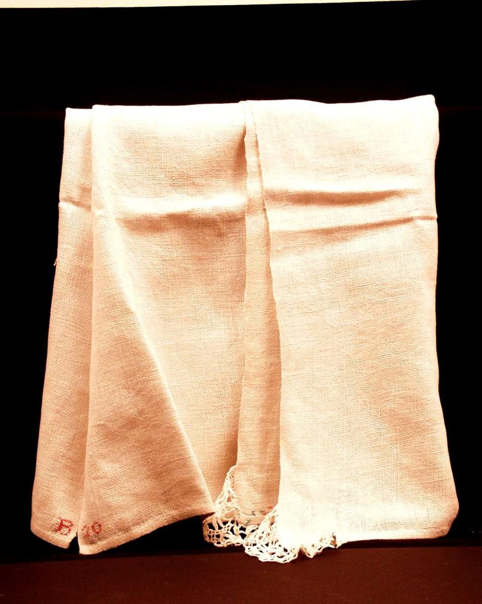 Benkeduk eller alterduk (?) i hvit grovvevet linstry. Jare i to sider. 1 cm håndfald i kortendene. I to hjørner er det påsydd, rynket, kjøpt blonde. Monogram B 20 i rød korssting.