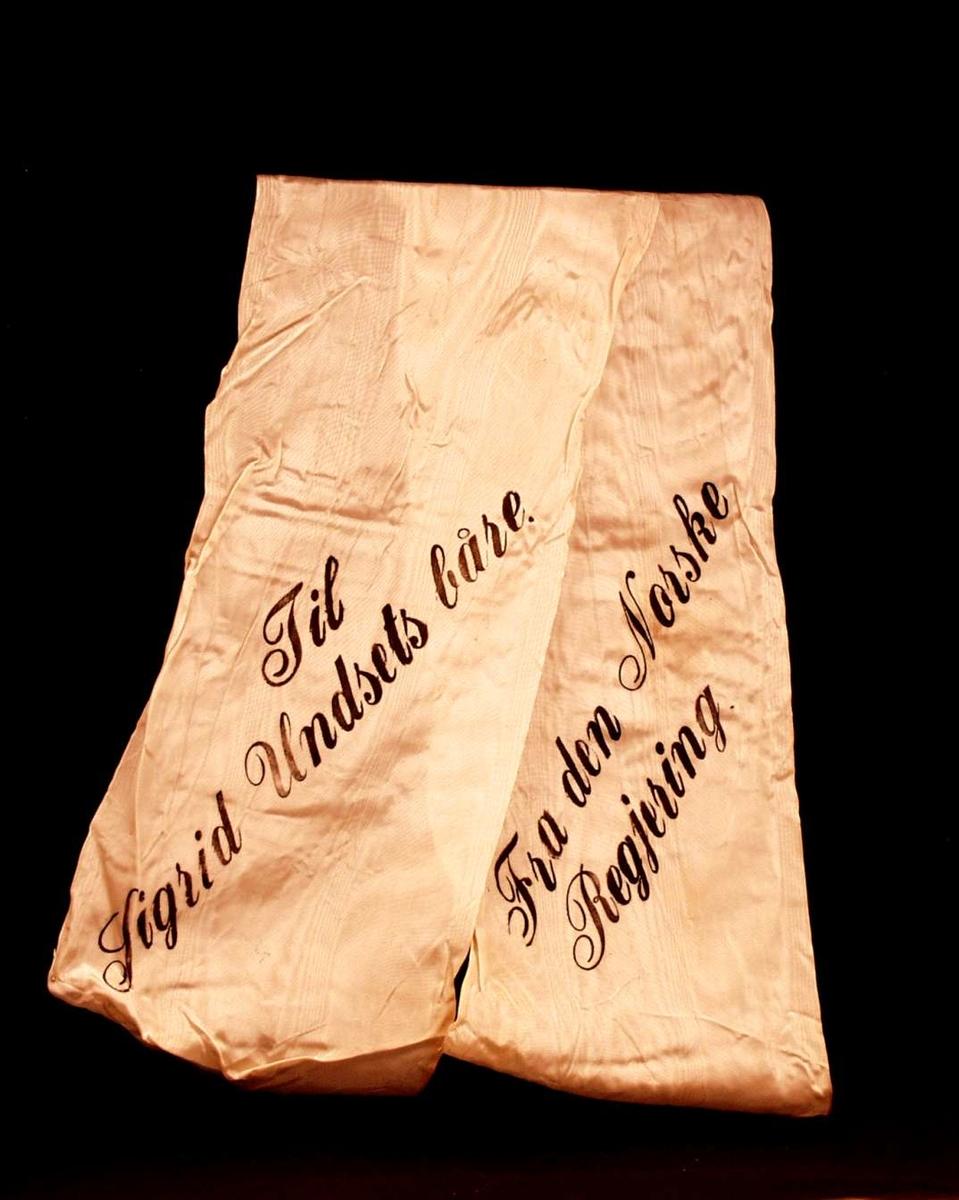 Bånd i kremfarget silke. Båndet er delt i to. På båndet står: Til Sigrid Undsets båre. Fra den Norske Regjering